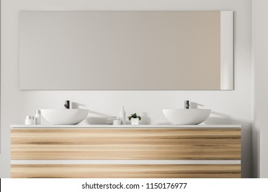 Double bathroom sink standing on a wooden countertop. A long mirror is hanging above it on a white wall. 3d rendering mock up