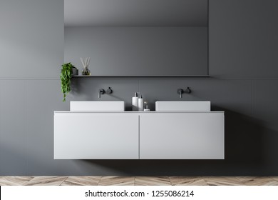 Double bathroom sink standing on white countertop in room with gray walls with a big horizontal mirror above it. 3d rendering