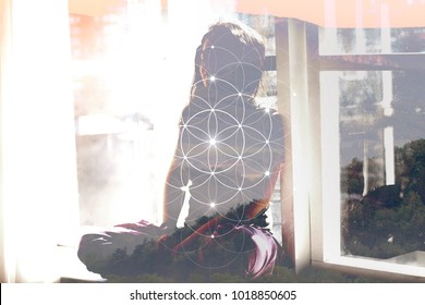 Double exposure art. Woman in meditation sitting in front of window with overlapping mountain landscape and sacred geometry interlocking circles flower of life symbol.