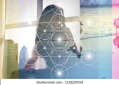 Double exposure collage with sacred geometry Metatron cube line art illustration with triangles, circles and shiny particles , young woman in meditation and overlaying images of sea and seagulls.