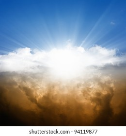 Dramatic background - bright sun in blue sky, white and dark clouds