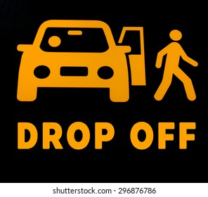 """""""DROP OFF"""" sign with illustrate of car and a man in orange with black blackground"""
