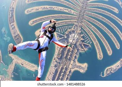 Dubai. Skydiving men rest on Dubai palm in free fall. Skydive Dubai.