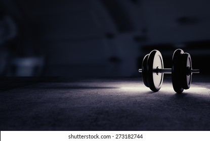 Dumbbell image with artistic rim lightning and big empty space for text on the left.