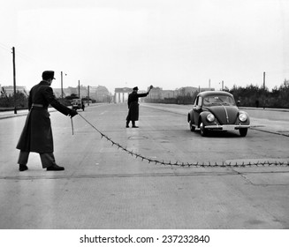 East Berlin customs police stopping a car on the Charlottenburger Chaussee with a tire puncturing heavy barbed chain Oct26.