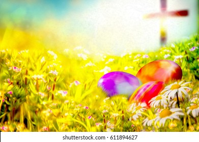 Easter background with colorful painted Easter eggs in the grass, with spring flowers and a cross in the background. Easter resurrection religious background with copy space for text.