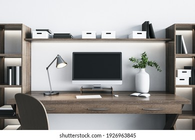Eco style wooden home workplace with modern computer monitor with blank black screen, white vase, steel lamp and white wall on background. 3D rendering, mockup