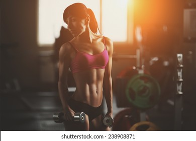 The effect of oil paints. Brutal fitness woman pumping up muscles with dumbbells. Brunette sexy fitness girl in pink sport wear with perfect body in the gym posing before training set