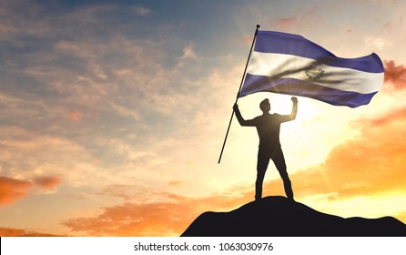 El Salvador flag being waved by a man celebrating success at the top of a mountain. 3D Rendering