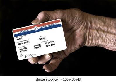An elderly female hand holds a mock United State government Medicare Health Insurance card. It is a generic card. This is a photo illustration.