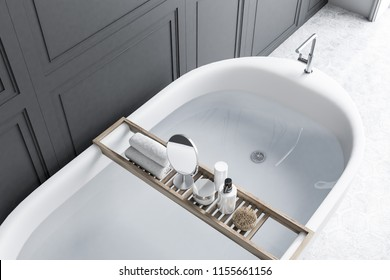 Elegant white bathtub filled with clear water standing in a luxury bathroom interior with gray walls, and a hexagon tile floor. A round mirror on a shelf. 3d rendering top view