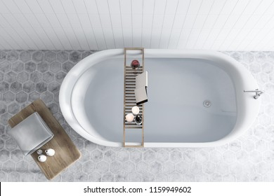 Elegant white bathtub filled with water standing in a luxury bathroom interior with white tiled walls, and a hexagon tile floor. A mock up open book on a shelf. 3d rendering top view