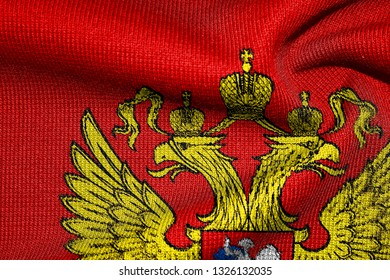 Emblem of Russia. Close-up of the emblem on the red fabric (knit, jumper).