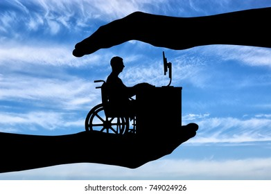 The employee is a disabled person in a wheelchair working with a computer at the table, he is in the hands of man. The concept of protection of the rights of persons with disabilities for employment
