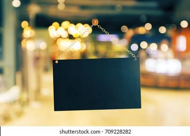 Empty black banner hanging on golden chain. Bokeh background. Ad concept. Mock up, 3D Rendering