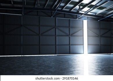 Empty building hangar with the door cracked open with room for text or copy space. Photo realistic 3d interior render