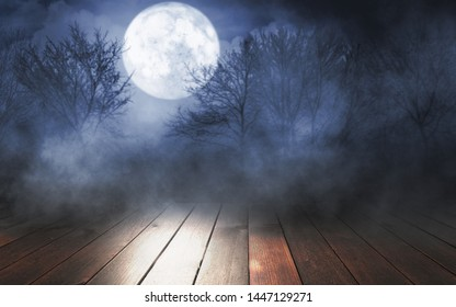Empty dark background. The glow of the moon in the forest, moonlight through the trees in the forest. Wooden table top