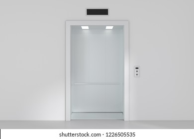 An empty modern elevator or lift with metal doors that are open.