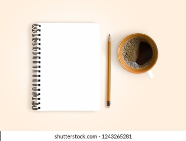 Empty notebook with pencil and cup of coffee on light orange background, table top view
