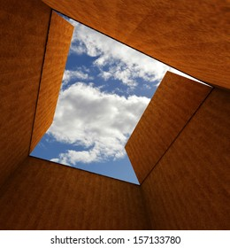 empty open cardboard box below the blue sky