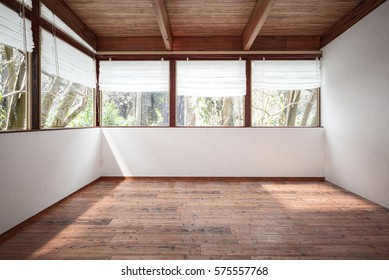 Empty room with white walls, wooden floor and ceiling with beams, with lots of windows and trees outside. 3d rendering.