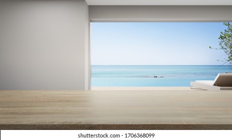 Empty table of bright dining room near terrace and lounge chair in modern beach house or luxury pool villa. White home interior 3d rendering with sea view.