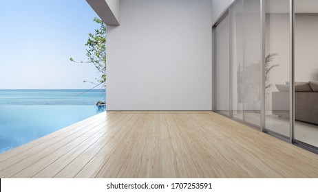 Empty terrace floor near living room and white wall in modern beach house or luxury pool villa. Wooden deck 3d rendering with sea view.