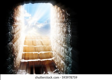 Empty tomb - Easter resurrection of Jesus Christ with stone rocky cave, bright sky and sun light beams or rays bursting