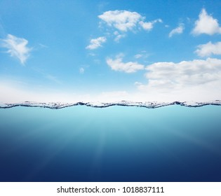 Empty underwater landscape with waterline and blue sky with clouds