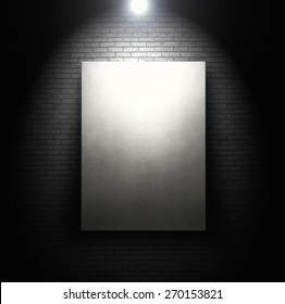 Empty white board in front of brick wall with spotlight