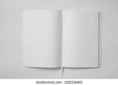 Empty white book in unfolded on a light background. Top view. Mock up. 3d rendering