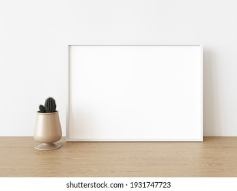 Empty white rectangular horizontal frame stands on light wood table against wall. Mockup of poster frame close up in home interior with cactus, 3D illustration