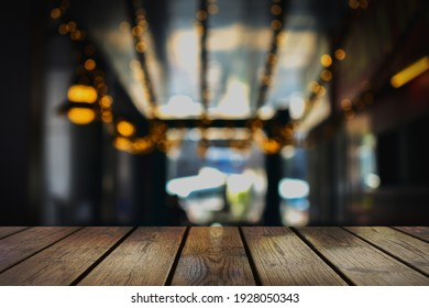 Empty wood table top and blur of night Restaurant background
