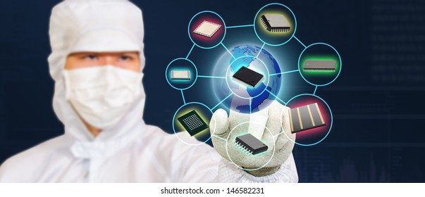 Engineer in working suit pointing globe and  electronics components