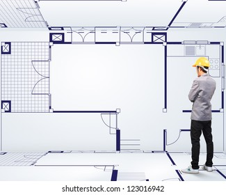 Engineering person standing near a House blueprints