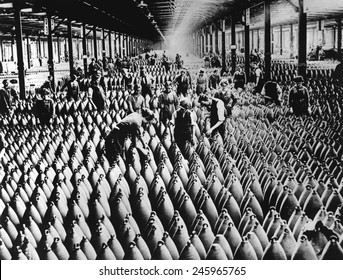 English women and men working in storage shed for large shells of a munitions factory. Artillery was the deadliest weapon of WWI, responsible for an estimated 60% of casualties. Ca. 1918.