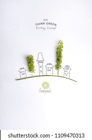 Environmentally friendly planet.Symbolic trees, made of green leaves and hand drawn cartoon sketches of a city houses. Minimal nature concept.Think Green. Ecology Concept.Flat lay.Top view.