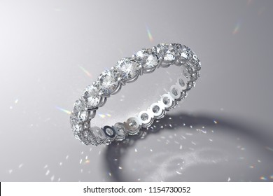 Eternity wedding ring with white round diamonds, shared prong setting. Colorful caustics rays on white background. 3D rendering