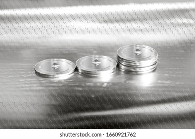 Ethereum (ETH) digital crypto currency. Stack of silver coins against the background of numbers. Cyber money. 3D Render.
