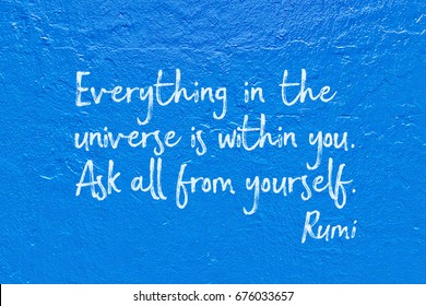 Everything in the universe is within you - ancient Persian poet and philosopher Rumi quote handwritten on blue wall