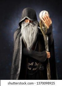 Evil Warlock old hooded wizard posing with staff on a blue gradient background. 3d rendering