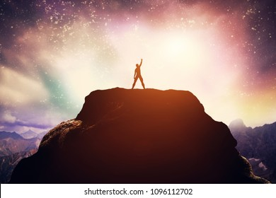 Excited man standing on the peak of a mountain. Success, achievement and victory.