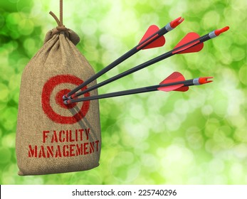 Facility Management - Three Arrows Hit in Red Target on a Hanging Sack on Green Bokeh Background.