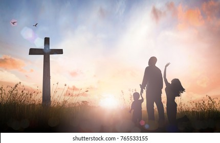 Faith concept: Silhouette christian family standing with cross for worship God on autumn sunset background