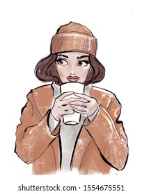 Fashion illustration: brunette girl with blue eyes and pink lips in the brown hat and coat, gray sweater holds in the hand white cup for hot beverages. Handdrawn. Isolation on white.