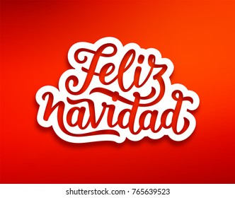 Feliz Navidad spanish Merry Christmas text on white paper label with carving over red background. Modern calligraphy lettering on sticker for season greetings.