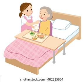 female caregiver feeding assistance to elderly