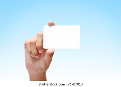 female hand holding white business card on blue background.
