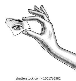 Female hand holds a mirror splinter in the fingers with eye reflection. Vintage engraving stylized drawing