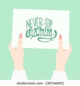 """Female hands with manicure hold white sheet with inscription """"Never Stop Dreaming"""" . Illustration."""